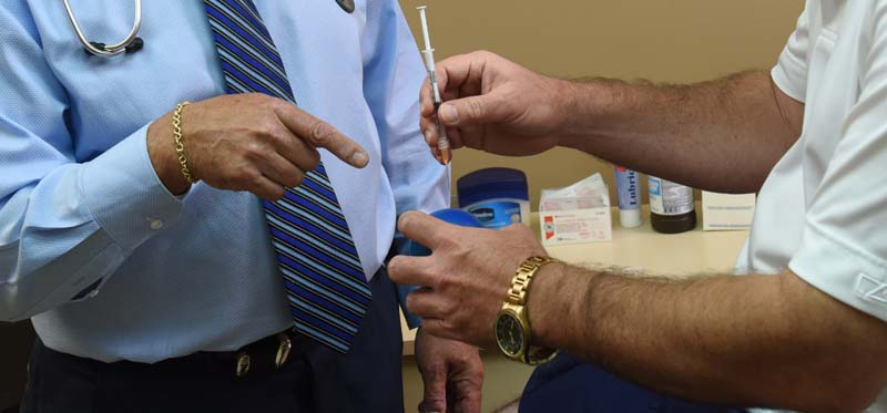 Dr. Berman showing a patient how to inject testosterone as part of the hormone therapy program